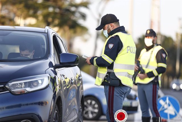 21 December 2020, Italy, Rome: A police officer checks motorists at a checkpoint at the Roma Nord toll plaza. From 21 December to 6 January, it is forbidden to travel between different Italian regions in order to contain the spread of the coronavirus. Pho