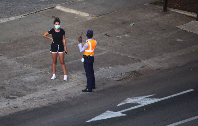30 August 2020, Cuba, Havana: A policeman talks to a woman wearing a face mask at a checkpoint, a curfew in Havana will be imposed from 1 to 15 September 2020 due to an increase in new coronavirus cases. Photo: Guillermo Nova/dpa