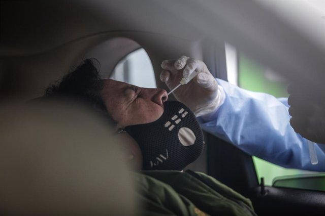 22 May 2020, Colombia, Bogota: A medical worker takes a sample of a driver at a drive-through COVID-19 testing centre which is launched by a private company in parking lots at the Colombian capital, where people could get tested without leaving their cars