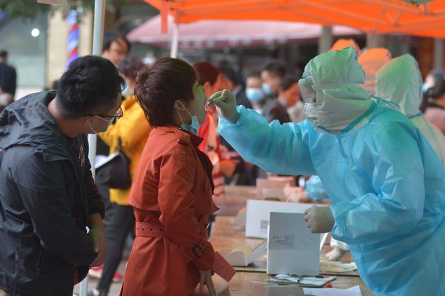 12 October 2020, China, Qingdao: A health worker takes a swab from a woman for the coronavirus test, after 9 people were found infected with the coronavirus (COVID-19) in Qingdao. Photo: -/TPG via ZUMA Press/dpa