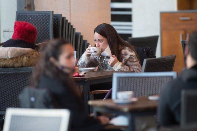 Una mujer toma un cafe en una terraza en Lugo