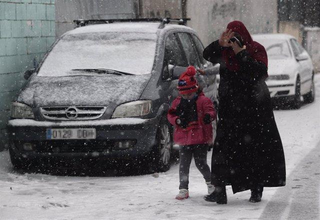 Una mujer y su hija caminan en la nieve en la Cañada Real Galiana
