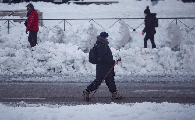 Varias personas caminan por el hielo que ha dejado la nieve alrededor de la Estación de Renfe de Alcorcón, en Madrid (España), a 11 de enero de 2021. Adif restableció ayer la circulación, interrumpida a causa del temporal de intensa nieve provocado por la