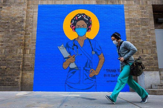 Un hombre pasa junto a un mural en Nueva York (EEUU) durante la pandemia de coronavirus