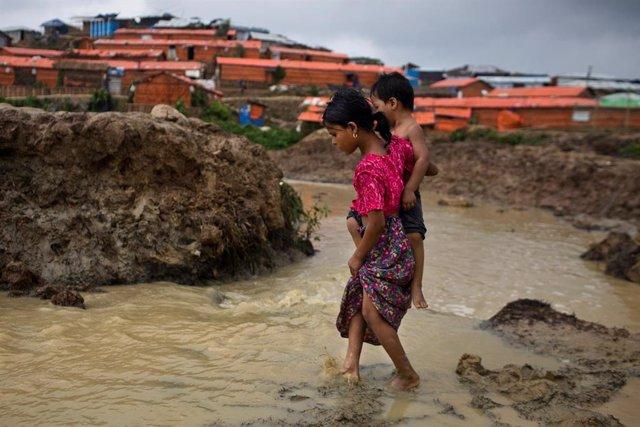 Una niña roghingya lleva a su hermano en un asentamiento de refugiados en Cox Bazar