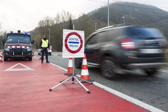 Un Mosso d'Esquadra durante el control policial por el confinamiento perimetral en la C-17 a la entrada de Ripoll, en Girona (España), a 24 de diciembre de 2020.