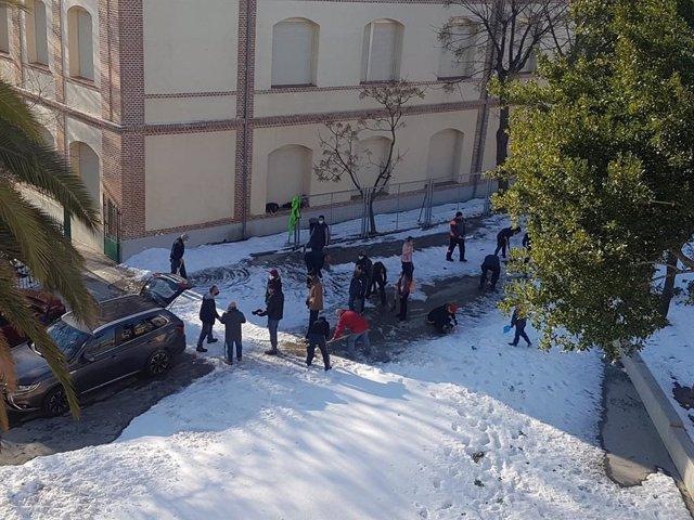 Familiares de alumnos colaboran en la limpieza de los accesos al colegio Vedruna, en Carabanchel