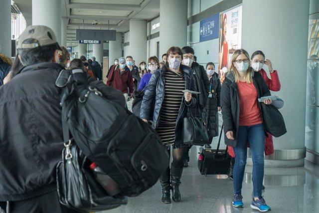 Personas con mascarilla en un aeropuerto.