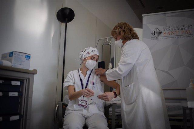 Una enfermera vacuna a un profesional sanitario con la vacuna de Pfizer-BioNtech contra el COVID-19 en el Hospital de la Santa Creu i Sant Pau de Barcelona