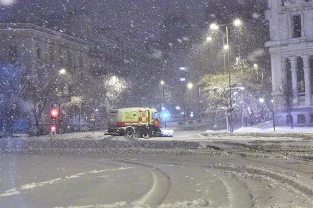 Una máquina quitanieves pasa junto al Ayuntamiento de Madrid, cubierto de nieve por la borrasca Filomena