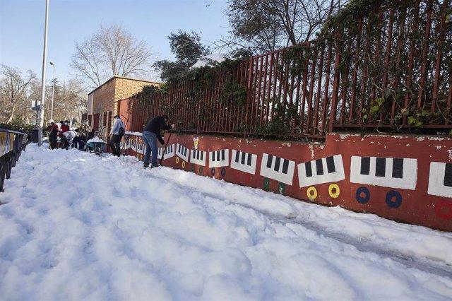 Varios familiares colaboran en la limpieza del hielo y la nieve en las inmediaciones del colegio Amadeo Vives tras la gran nevada por el paso de la borrasca 'Filomena', en Madrid, (España), a 16 de enero de 2021.