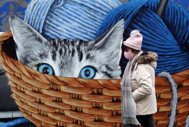 Una dona amb mascareta al costat d'un mural amb un gat a Glasgow