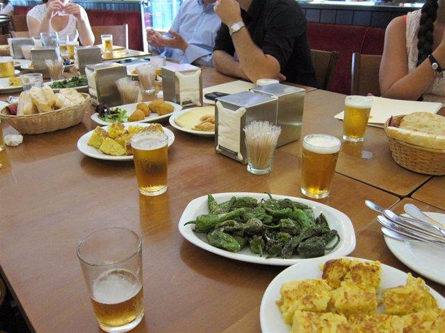 Una mesa con comida y bebida en un bar.