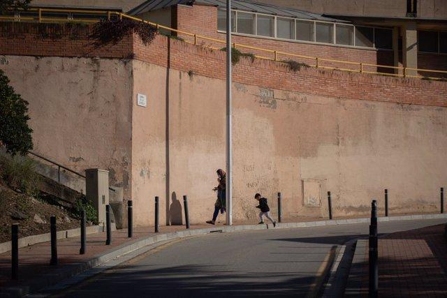 Una dona amb un nen caminen per un carrer del barri de Ciutat Meridiana.