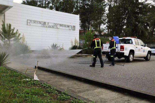 Operarios del Grupo Municipal de Emergencias desinfectan la fachada de la Residencia de Mayores de O Carballiño