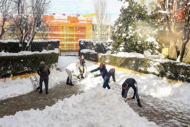 Vecinos de la localidad de Pozuelo de Alarcón ayudan a retirar la nieve de las calles en Madrid (España) a 11 de enero de 2021. Madrid afronta hoy el primer día laborable en la región tras la gran nevada provocada por el paso de la borrasca 'Filomena'. Nu
