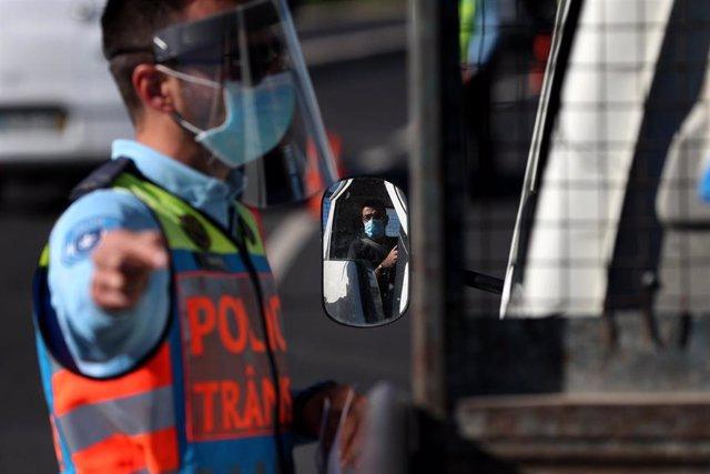Un policía con mascarilla en Portugal en un control por las restricciones impuestas por el coronavirus
