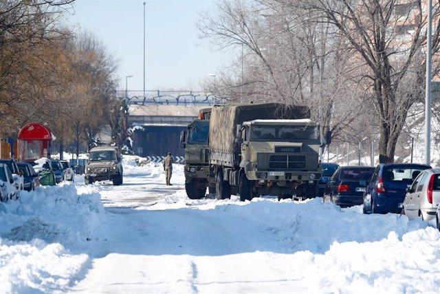 Un camión de la Unidad Militar de Emergencias (UME) colabora en la retirada de nieve y hielo en las inmediaciones del colegio Fuente de la Villa tras la gran nevada provocada por la borrasca 'Filomena', en Valdemoro (Madrid)