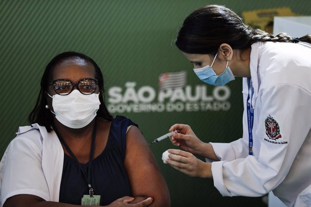17 January 2021, Brazil, Sao Paulo: Brazilian nurse Monica Calazans (L) receives his dose of the Coronavirus (Covid-19) vaccine by a health worker during a vaccination campaign. Brazil's National Health Surveillance Agency has granted emergency approval t