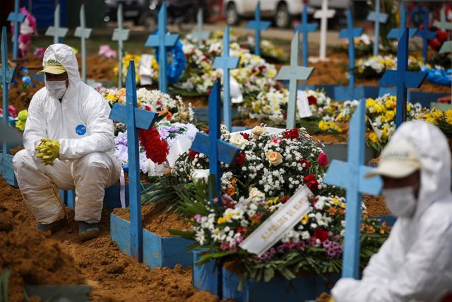 15 January 2021, Brazil, Manaus: Cemetery workers in protective suits carry the coffin of a person who died of Covid-19 at Nossa Senhora Aparecida Cemetery. Photo: Lucas Silva/dpa