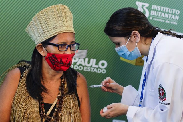 17 January 2021, Brazil, Sao Paulo: A woman receives his dose of the Coronavirus (Covid-19) vaccine by a health worker during a vaccination campaign. Brazil's National Health Surveillance Agency has granted emergency approval to each of Sinovac's and Astr