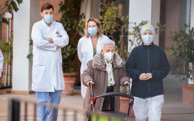 Araceli y Mónica, la residente más longeva de la Residencia de mayores Los Olmos y la sanitaria más joven, acompañadas de personal del geriátrico, tras recibir la segunda dosis de la vacuna Pfizer-BioNTech, en Guadalajara, Castilla-La Mancha.
