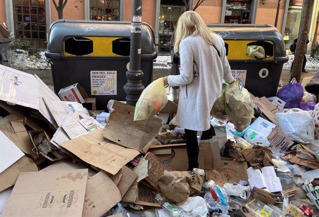 Una mujer tira dos bolsas de basura donde hay acumuladas otras tantas decenas de bolsas en un punto de Alonso Martínez, en Madrid (España).