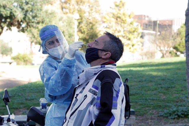 05 January 2021, Greece, Athens: A medical staff member of the National Health Organization (EODY) conducts a Coronavirus (Covid-19) rapid test on a motorbike driver at a drive-through testing site. Photo: Aristidis Vafeiadakis/ZUMA Wire/dpa