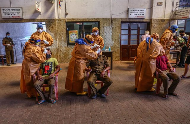 12 October 2020, Sri Lanka, Colombo: Sri Lankan health officials take swabs from people for coronavirus (COVID-19) tests at Fort railway station. Photo: Pradeep Dambarage/ZUMA Wire/dpa