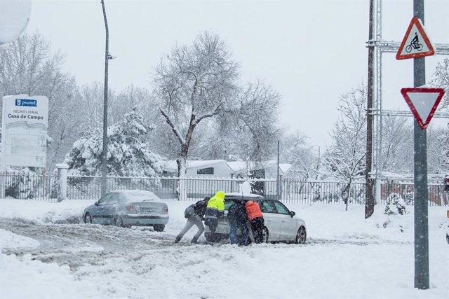 Varias personas ayudan a sacar un coche atrapado por la nieve durante la gran nevada provocada por la borrasca 'Filomena'.