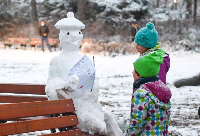 Dos niños junto a un muñeco de nieve en Frankfurt, Alemania
