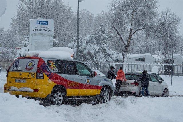 Una ambulancia ayuda a sacar un coche atrapado por la nieve durante la gran nevada provocada por la borrasca 'Filomena',  en Madrid (España), a 9 de enero de 2021. La borrasca 'Filomena' ha provocado una intensa nevada en la Comunidad de Madrid, principal