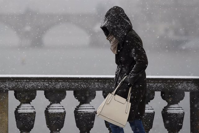12 January 2021, Czech Republic, Prague: A woman walks amid snowfall on a snow-covered pathway. Photo: Ondej Deml/CTK/dpa