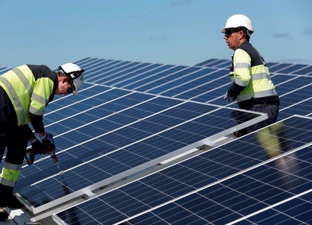 Dos operarios fijan paneles solares en la instalación
