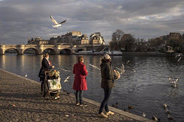 Mujeres con mascarilla junto al río Sena en París, Francia