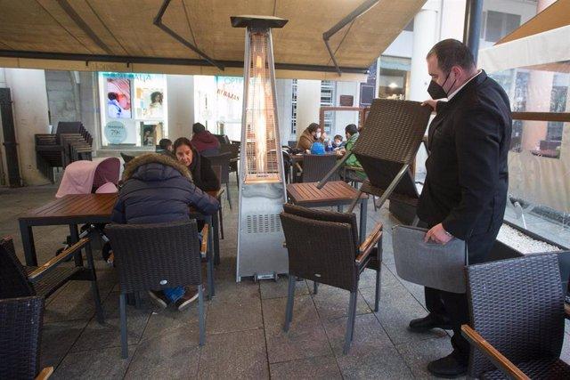 Un camarero recoge las sillas y mesas el primer día del cierre perimetral decretado en Lugo a 15 de enero de 2021