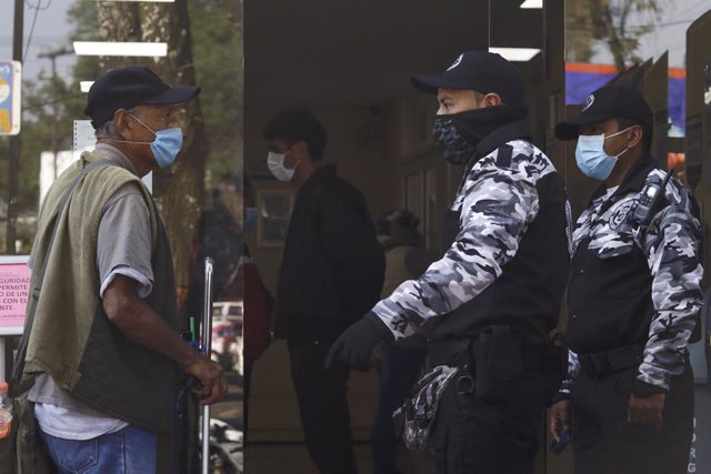 18 March 2020, Mexico, Mexico City: Police officers stop a man wearing a face mask to prevent the spread of Coronavirus (Covid-19), in the vicinity of the National Institute of Respiratory Diseases. Photo: Paola Hidalgo/NOTIMEX/dpa