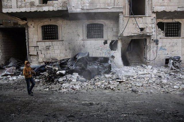 Un niño camina frente a un edifico bombardeado en la provincia de Idlib, en el noroeste de Siria