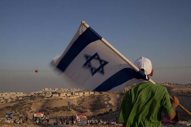 Un colono con una bandera israelí en el asentamiento isarelí de Maale Adumim, en Cisjordania