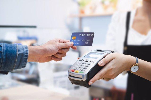 Una persona pagando con tarjeta de crédito en un datafono de un comercio