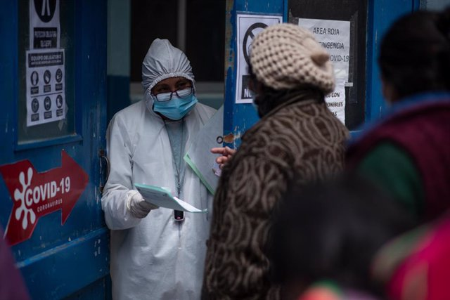 15 January 2021, Bolivia, La Paz: A health worker answers questions from people outside the emergency room at de Clinicas Hospital. Photo: Radoslaw Czajkowski/dpa