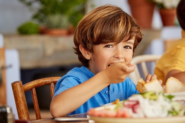 Portrait of boy eating food at table in house