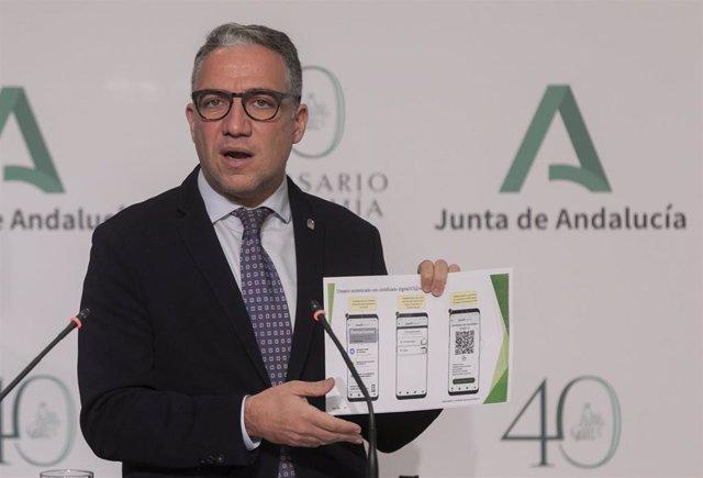 El consejero de la Presidencia, Administración Pública e Interior, y portavoz del Gobierno andaluz, Elías Bendodo, enseña una muestra del certificado de vacunación de Covid-19, durante su intervención en la rueda de prensa posterior a la reunión del Conse