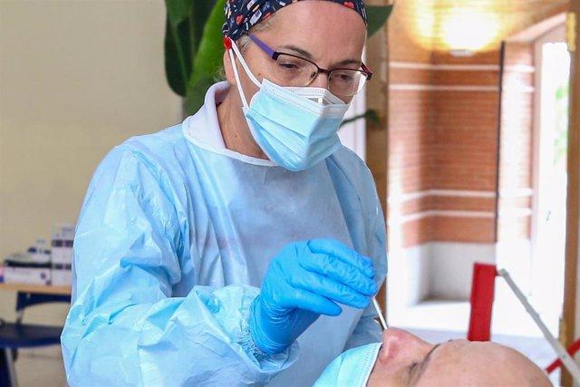 Una sanitaria realiza un test de antígenos a un hombre en un dispositivo organizado por la Comunidad de Madrid para la detección del COVID-19 en policías locales, miembros de Protección Civil, Bomberos, Agentes Forestales y gestores del 112, en el Institu