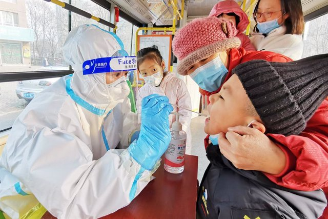 23 December 2020, China, Dalian: A health worker takes a swab from a child for a coronavirus test at Ganjingzi district during a mass testing campaign. Photo: Liu Debin/SIPA Asia via ZUMA Wire/dpa