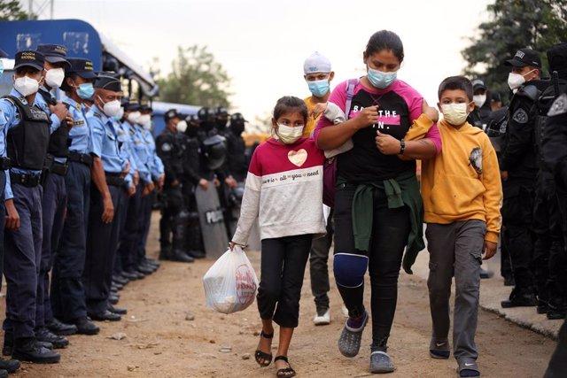 Una mujer y sus hijos atraviesan un punto de control de la Policía de Honduras en la andadura de la nueva caravana migrante que ya ha llegado a Guatemala.