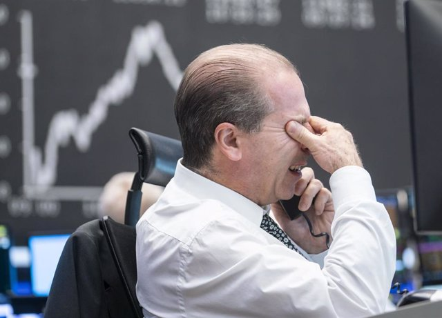04 November 2020, Hessen, Frankfurt: A trader sits in the trading room of the Frankfurt Stock Exchange in front of his monitors, as the Dax curve can be seen in the background. Photo: Frank Rumpenhorst/dpa