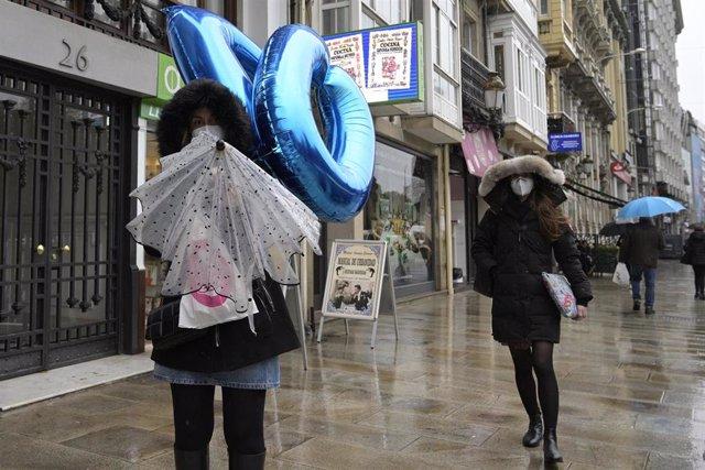 Transeúntes caminan protegidos por una vía de A Coruña, Galicia (España), a 20 de enero de 2021. El temporal de nieve y posterior frío provocado por la borrasca 'Filomena' terminará este martes cuando ésta pase el testigo a un nuevo frente, bautizado por