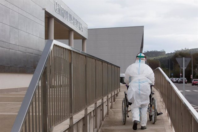 Un trabajador sanitario totalmente protegido acuden a buscar a un anciano de la residencia de ancianos de San Cibrao donde se ha originado un brote de Covid-19, en San Cibrao, Lugo, Galicia, (España), a 9 de noviembre de 2020. En el centro la situación ac