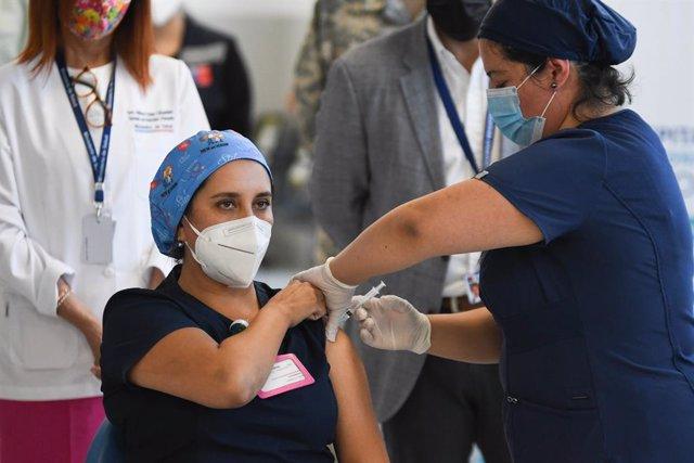 18 January 2021, Chile, Antofagasta: A nurse receives a Pfizer-Biontech Coronavirus vaccine dose during the vaccination campaign for the medical staff. Photo: Camilo Alfaro/Agencia Uno/dpa